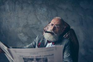barbat fumeaza in fotoliu citind ziarul